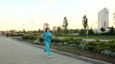 Adult woman jogging through a large garden