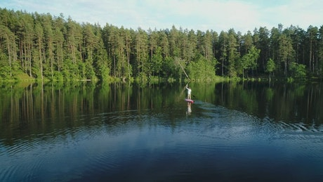 Adventurer woman on a paddleboard in the lake