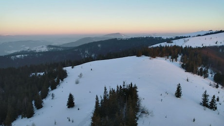 Aerial pan shot over a winter mountain rage