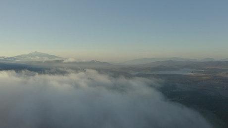 Aerial tour above a cloudy natural landscape
