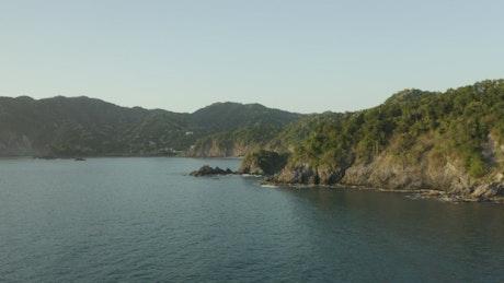 Aerial tour around a coastline on a sunny day