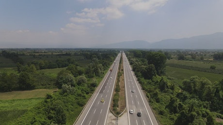 Aerial tour of a highway surrounded by nature