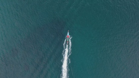 Aerial tracking shot of a boat in the sea