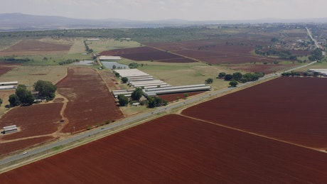 Aerial view of a freeway with farms next to it