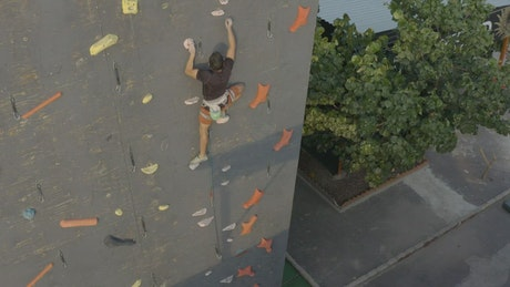 Aerial view of a mountaineer on top of a wall to climb