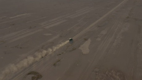 Aerial view of a pickup truck traveling through a desert
