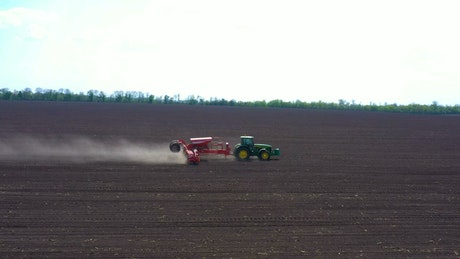 Aerial view of a tractor working on the dirt field
