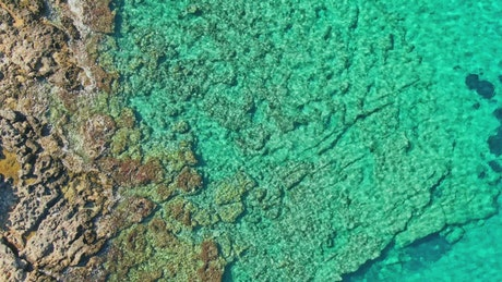 Aerial view of bright blue rocky sea shallows