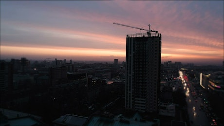 Aerial view of city construction crane at sunset