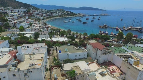Aerial view of house, beach and  a marina in a blue ocean