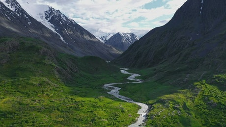 Aerial view of lush river valley and snowy mountains