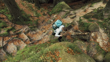 Aerial view of man climbing mossy rocks on hike