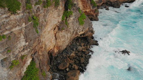 Aerial view of turquoise waves crashing on cliffs