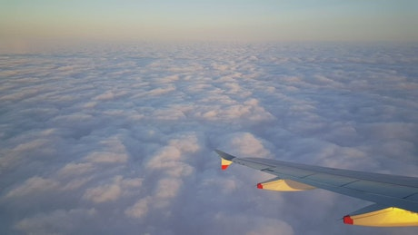 Airplane flying above beautiful fluffy clouds