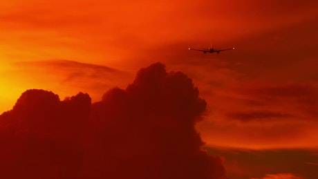 Airplane flying in a red cloudy sky