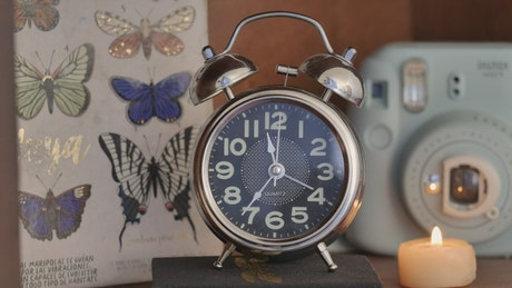 Alarm clock on a table while time flies by