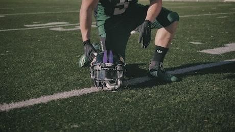 Amateur football player putting on his helmet