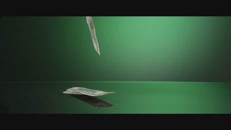 American dollars falling down on a green surface