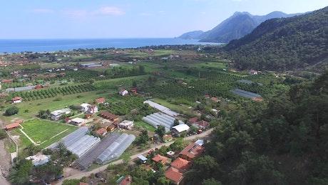 An agricultural plain near sea and forest