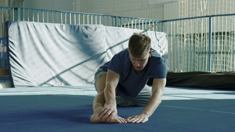 An athlete stretching in the gym