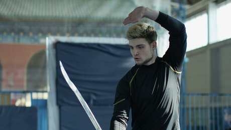 An athlete training with a sword