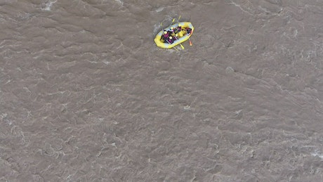 An in inflatable yellow boat sailing in the rapid rivers