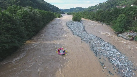 An inflatable boat sailing the river rapids