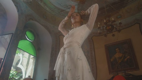 An old fashioned woman spins in a white dress