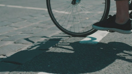 An urban cyclist and his shadow in the road