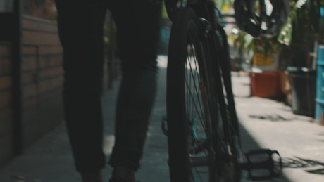 An urban cyclist walks with his bike