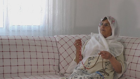 Anciana rezando el Corán con un rosario