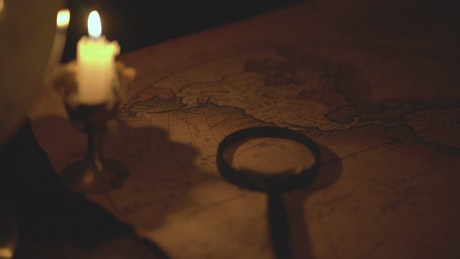 Ancient map of the world in the dark lit by candlelight