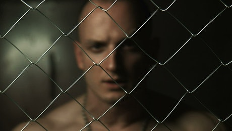 Angry prisoner behind a wire fence