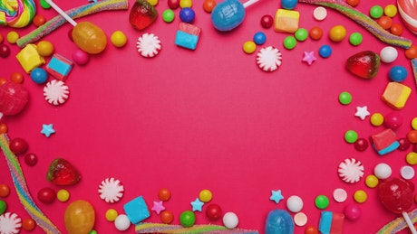 Animated stop motion frame of candies on a pink background