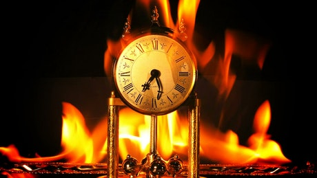 Antique clock burning on black background