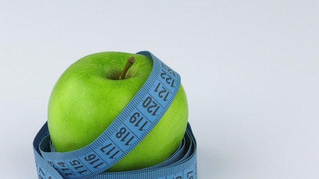 Apple and measuring tape on white background
