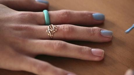 Applying blue nail polish to a woman hand