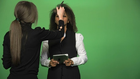 Applying make up to news presenter