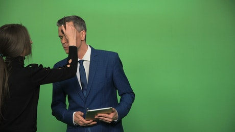 Applying make up to newscaster on a green screen