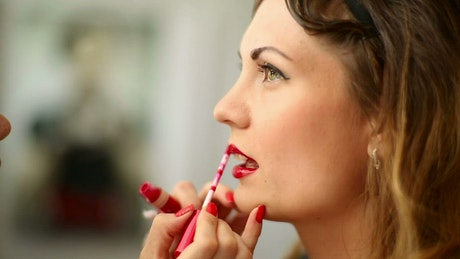 Applying red lipstick on a woman