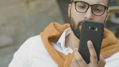Arab man smiles while using mobile app