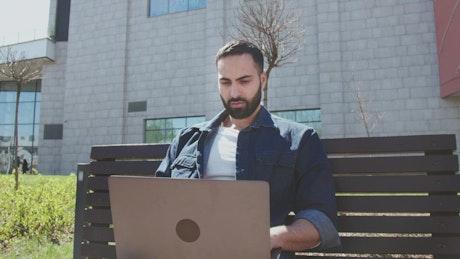 Arab man works on laptop outside office building