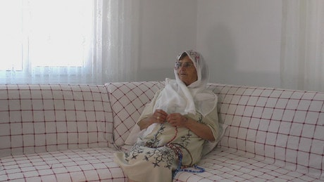 Arab old woman praying with a rosary at home