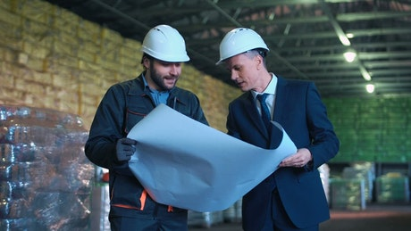 Architect and worker fighting in the warehouse
