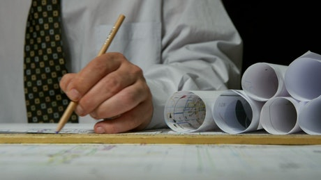 Architect drawing lines on plans