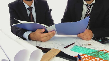 Architects in suit reviewing papers in a folder
