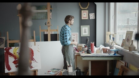Artist gazes out window in painting studio