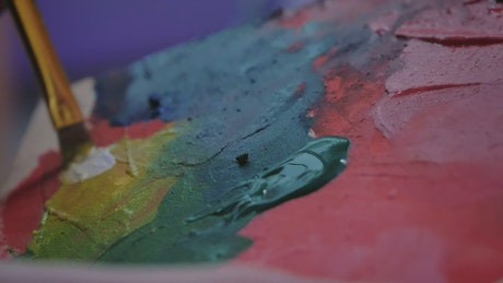 Artist mixing paint on a palette