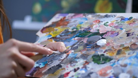 Artist mixing paints on a board