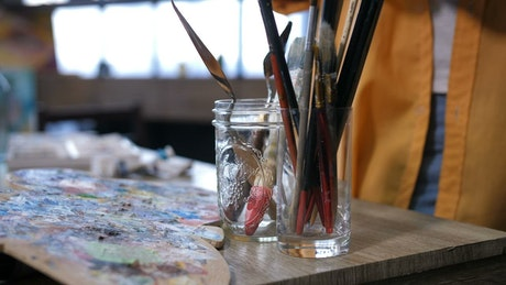 Artist placing a cup down in their studio